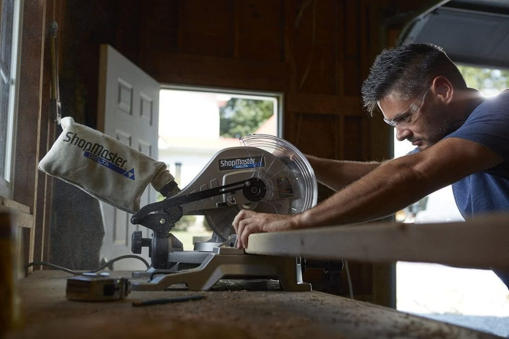 Man Works with Delta Master Miter Saw with Laser