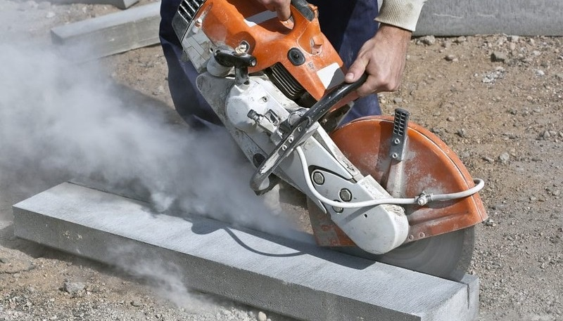 man cuts concrete with a saw